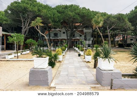 ALBANIA GOLEM- September 20 2015: The road through a sandy beach to a guest two-storey house surrounded by green trees in the resort of Golem.