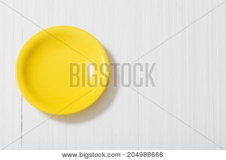 the yellow plate on white wooden background