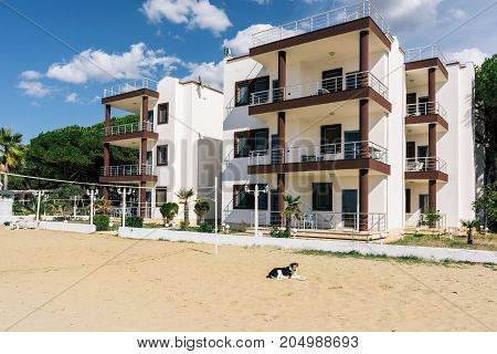 ALBANIA GOLEM- September 21 2015: Guest three-storey houses with balconies on the coastal line of the Adriatic Sea sandy beach with a volleyball court