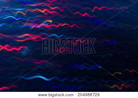 Abstract background of colorful waves in motion on black. Bokeh of defocused curves, blurred neon blue and purple leds, festive backdrop of serpantine, holidays and celebrations