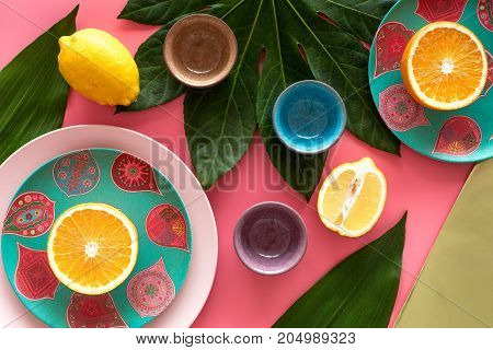 Crockery pattern. Cups and plates near tropical leaves and fruits on pink background top view. poster