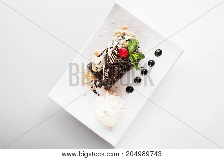 Chocolate pie on white square cut plate with decoration from cherry, almond and mint. Delicious dessert serving in restaurant with ice-cream ball, top view with free space on background