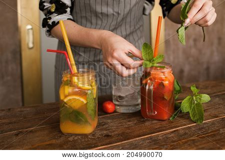 Waiter decorates fruit cocktails by mint. Fresh citrus and strawberry cold drink with ice on wooden table, concept of refreshment and satisfying thirst in summer