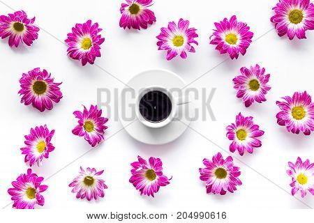 Floral pattern with cup of coffee on white background top view.