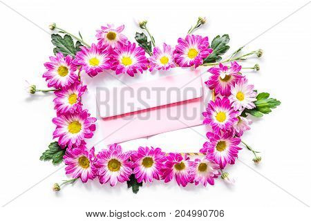 Floral pattern. Envelope in frame of pink flowers on white background top view.