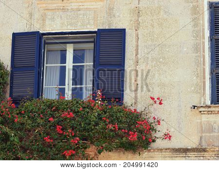 Opened window on the yellow wall with red flowers