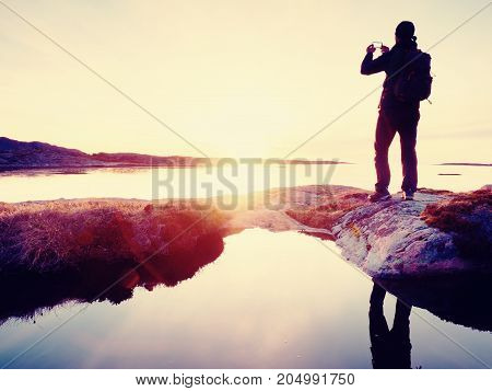Rear Silhouette Of Travelling Man Taking Selfie At Sea. Tourist With Backpack Standing On A Rock