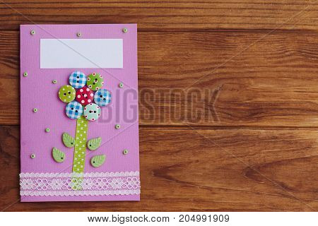Greeting card made by a child for mothers day, fathers day, March 8, birthday. Paper card with a flower from wooden buttons. Wooden background with copy space for text. Top view