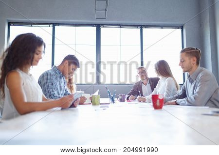 Young business staff discussing work on a meeting room background. Students on a start-up conference. Group business project concept.