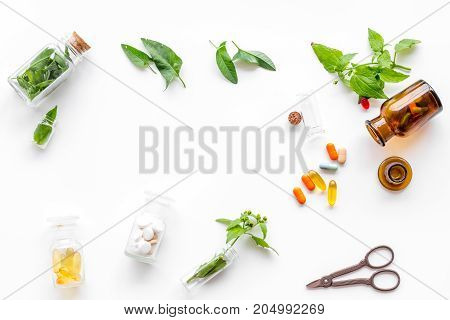 Harvest medicinal herb. Leaves, bottles and sciccors on white background top view.