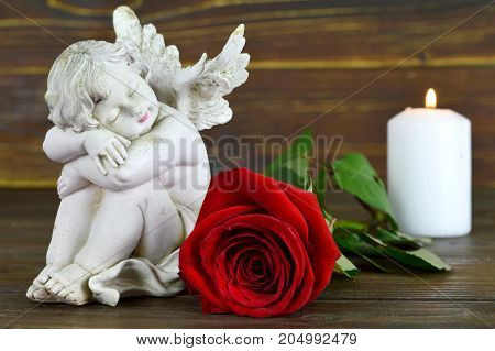 Condolence card with angel figurine, red rose and white candle