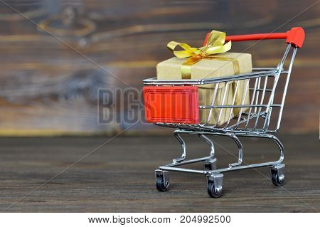 Shopping cart with gift box on wooden background