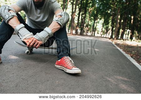 Professional skater after hard competitions. Extreme sport challenge and training, exhaustion and refreshment concept. Skateboarder modern urban lifestyle and culture