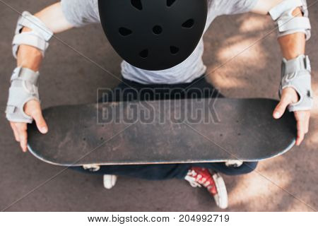 Skateboard halmet, elbow and gloves protection on unrecognizable skateboarder. Extreme sport challenge and training, motivation for win in competition