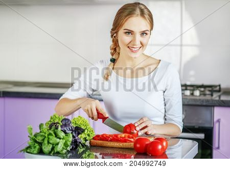 A young woman is preparing food in the kitchen. Vegetarian. The concept is healthy food diet vegetarianism weight loss.