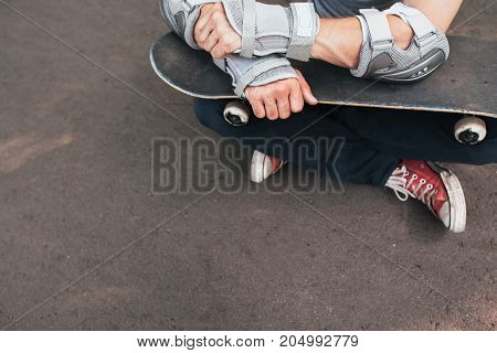Professional skater sitting with skate, ready to next competition. Extreme sport challenge and training, skateboarder modern lifestyle and culture of young people background with free space