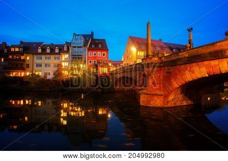 View of Karlsbrucke and Old town of Nuremberg over Pegnitz river at night, Germany, retro toned