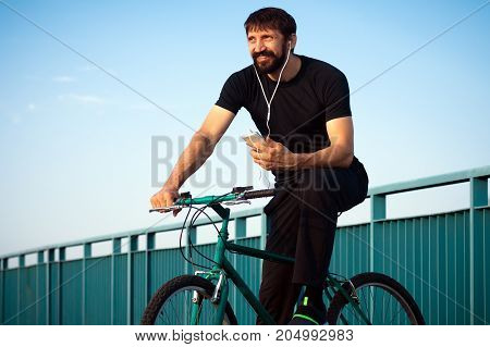 The smiling bearded man with earphones is listening music and sitting on bicycle.