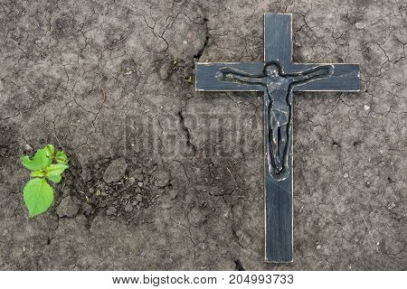 Black Wooden Crucifix On The Ground Background With A Green Plan