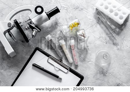 Laboratory test. Microscope, pills, test tube on grey stone background top view.