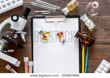 Laboratory test. Microscope, pills, test tube on wooden background top view.