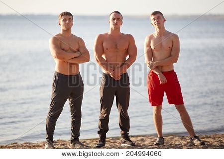 Three gorgeous guys standing shirtless on a beach on a blurred river background. Athletes with perfect torsos and muscles.