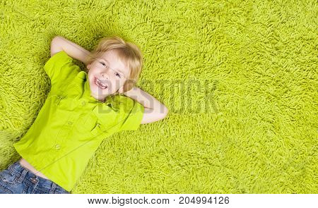 Child Lying Over Green Carpet. Happy Smiling Kid Boy Five Years Old Top View