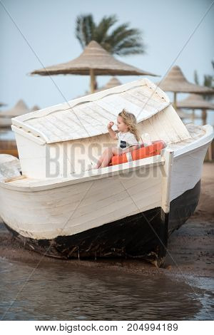 Boy little child sitting in life ring. Small kid sit on wooden boat at beach. Marine safety and transport. Childhood and baby care concept. Happiness and expressive emotions.