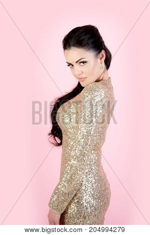 Girl with brunette hair on pink background. Woman in party dress with golden sequins. Fashion and style. Beauty and makeup. Holidays birthday new year christmas xmas anniversary celebration