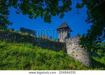 Stone fortification on green hill on blue sky. Landmark and travel destination. Bastion on sunny summer day. Protection and defense concept. Castle tower and wall.