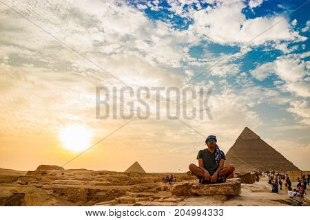 the man with the desert and the pyramids on the background in Cairo, Egypt