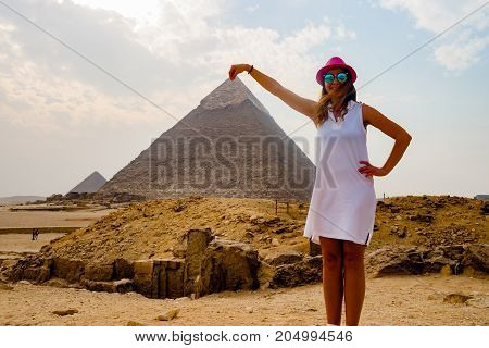 A beautiful girl holding a pyramid in Cairo, Egypt