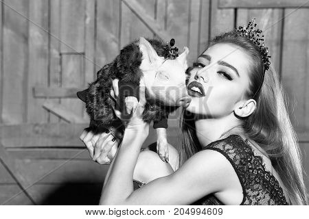 Portrait of elegant stylish young sensual woman in thin rim holding and kissing cute little pig in hands in fur coat indoor on wooden background vertical picture