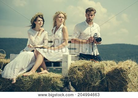 Friends or people relaxing on nature. Women or girls reading books on bench on sunny day. Man or macho with camera on cloudy sky. Hobby and lifestyle concept. Summer vacation and wanderlust.