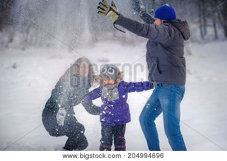 the happy family plays snowballs in the wood there is a lot of snow