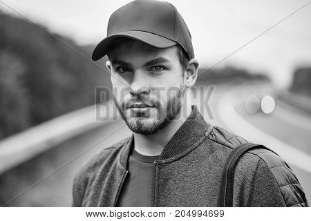 Young man with beard on his serious sexy handsome face in dark casual jacket and red baseball cap on head on background of road way outdoor