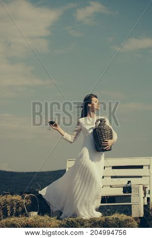Model with alcohol drink on sunny day. Girl in white dress posing on grey sky. Summer vacation holidays and celebration. Winery tour concept. Woman with glass of red wine and wicker bottle.