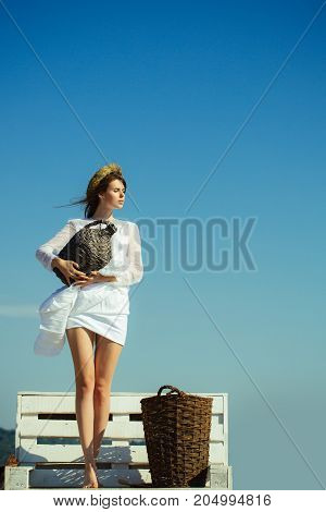 Winery tour concept. Harvesting and winemaking. Woman with wicker bottle and basket standing on bench. Summer vacation holidays and celebration. Girl in white dress and wreath on blue sky copy space