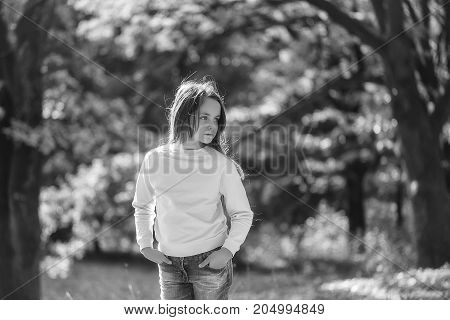 Cute girl preteen with serious face in casual clothes posing with her hands in pockets on background of foliage in forest