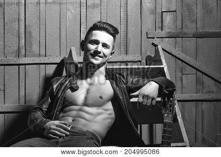Handsome sexy sensual muscular stylish young man in leather jacket with bare torso sitting indoor near stairs on wooden background horizontal picture