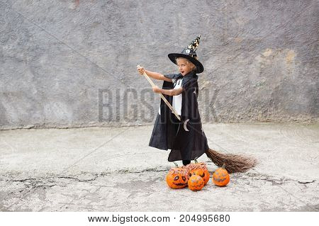 Girl in Halloween costume having fun. A little girl in a witch costume is playing. Little girl in witch costume playing outdoor. Little girl witch with a broom