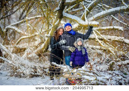 happy family poses under a tree in the winter wood cheerful winter entertainments everything is covered with snow around
