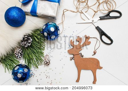 Holiday preparation. Christmas and New Year. Handmade wooden deer with ornament blue balls, gift box and pine branch laying on desk, top view with copy space. Home and restaurant decoration concept