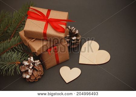 Wrapped christmas or other holiday handmade present in craft paper with red ribbon. Present box, decoration of gift on white wooden table, top view with copy space, pinecones fir branches.