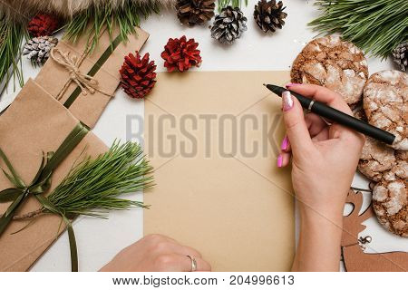 Presents, greeting card and congratulation with Christmas and New Year holidays. Woman starts to write on piece of paper. Wrapped gifts, decoration from pine, strobila and sweet cakes nearby, top view