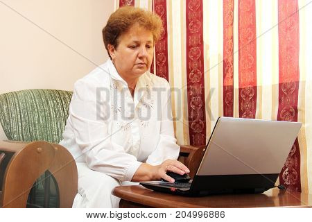 Old Woman With Laptop. Senior Grandmother Indoors With Notebook. Web Surfing And Shopping On The Int