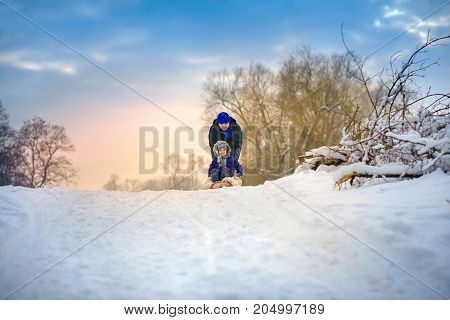 the happy family rides the sledge in the winter wood cheerful winter entertainments everything is covered with snow around