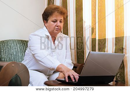 Old Woman With Laptop. Senior Lady Indoors. Web Surfing And Shopping On The Internet. Social Network