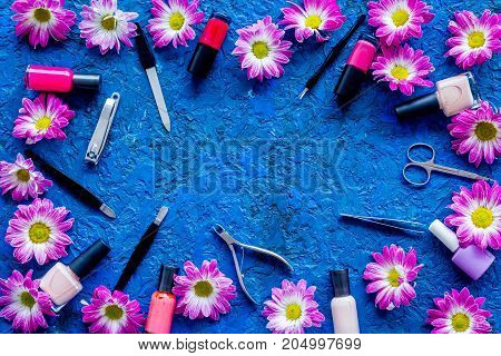 Preparing for manicure. Tools and nail polishes on blue background top view.
