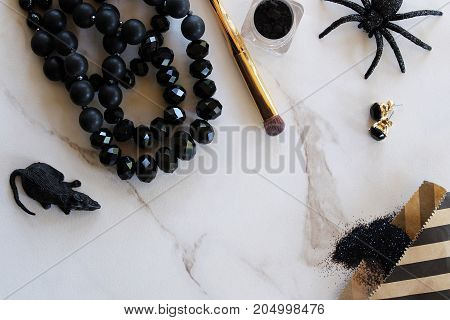 Halloween party supplies, fashion and beauty items styled on white marble desk. Copy space.
